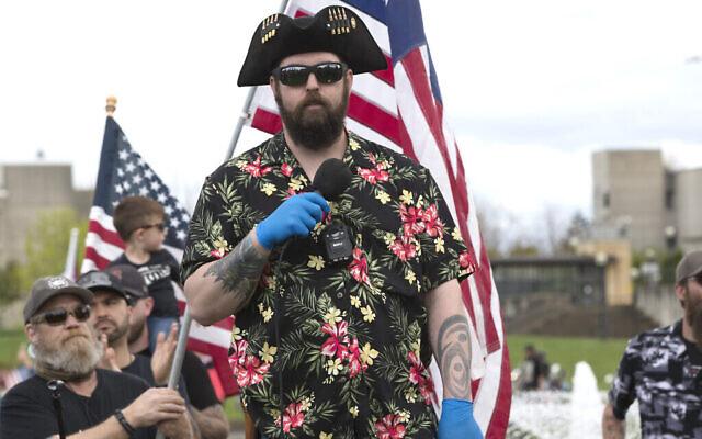Matt Marshall du groupuscule de droite Washington State Three Percent (3%), vêtu de l'uniforme des Boogaloo - une chemise hawaïenne - prend la parole lors d'un rassemblement contre le confinement devant le Capitole d'Olympia, dans l'État de Washington, le 19 avril  2020. (Crédit : Karen Ducey/Getty Images via JTA)