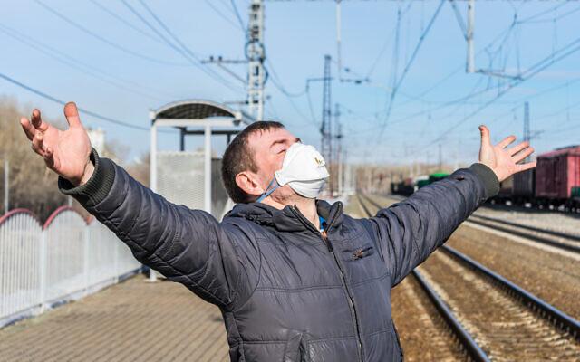 Image d'illustration : un homme heureux, guéri de la maladie, debout dans une gare portant un masque. (Crédit : iStock / Nikolay Chekalin)