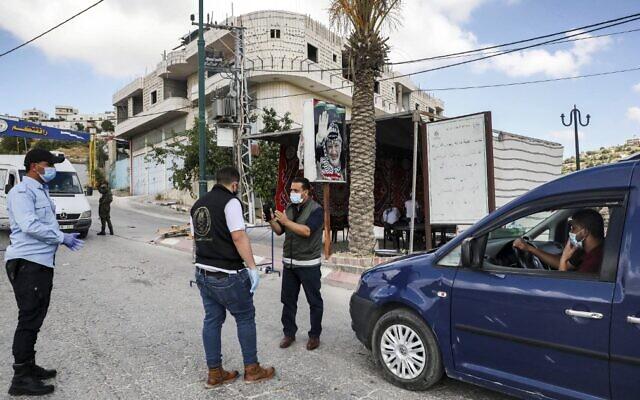 Les forces de sécurité palestiniennes portant des masques se trouvent à un point de contrôle dans le village de Tafouh, à l'ouest de Hébron en Cisjordanie, le 19 juin 2020, tout en imposant un bouclage en raison d'une recrudescence de nouveaux cas de coronavirus (HAZEM BADER / AFP)