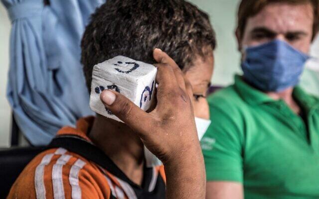 """Un travailleur social joue à un jeu avec un enfant des rues dans l'une des unités mobiles gérées par les autorités égyptiennes et utilisé dans le cadre du programme social """"Atfal bala ma'wa"""" (Enfants sans foyer), dans le quartier de l'Abbasia, dans la capitale du Caire, le 22 juin 2020. (Khaled DESOUKI / AFP)"""