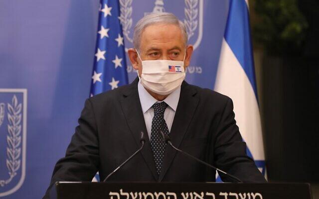 Le Premier ministre Benjamin Netanyahu porte un masque facial contre la COVID-19, portant les drapeaux américain et israélien, lors d'une conférence de presse avec le représentant spécial des États-Unis pour l'Iran (hors-champ) au bureau du Premier ministre à Jérusalem, le 30 juin 2020. (Abir Sultan/POOL/AFP)
