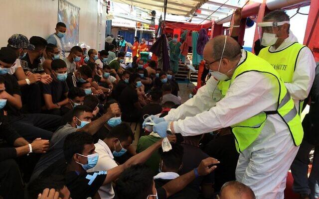 Un agent de santé italien donne des bracelets numérotés aux migrants secourus en mer sur le navire de sauvetage «Ocean Viking», exploité par l'ONG française SOS Méditerranée en mer Méditerranée, le 5 juillet 2020. (Shahzad ABDUL / AFP)
