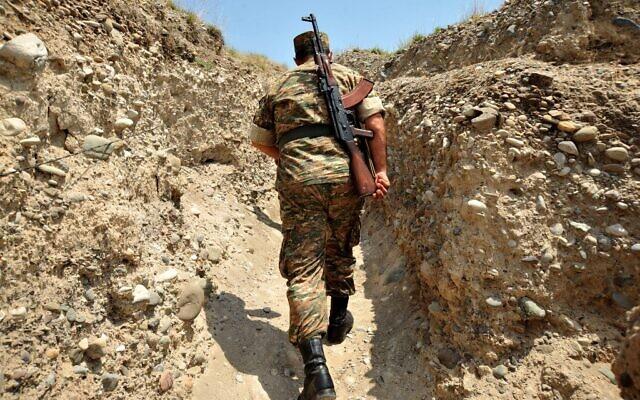 Un soldat arménien de la république autoproclamée du Haut-Karabagh marche dans une tranchée sur la ligne de front à la frontière avec l'Azerbaïdjan près de la ville de Martakert, le 11 juillet 2012. (KAREN MINASYAN / AFP)