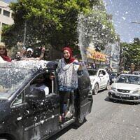 Des lycéens palestiniens lancent de la neige artificielle depuis une voiture alors qu'ils fêtent l'annonce des résultats des examens finaux du lycée à Hébron, en Cisjordanie, le 11 juillet 2020 (Crédit : HAZEM BADER / AFP)
