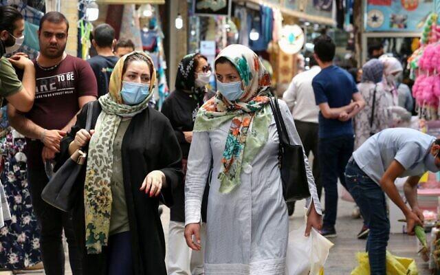 Des Iraniennes, portant des masques en raison de la pandémie de COVID-19, font leurs courses au bazar de Tajrish dans la capitale iranienne, Téhéran le 14 juillet 2020. (Crédit : ATTA KENARE / AFP)