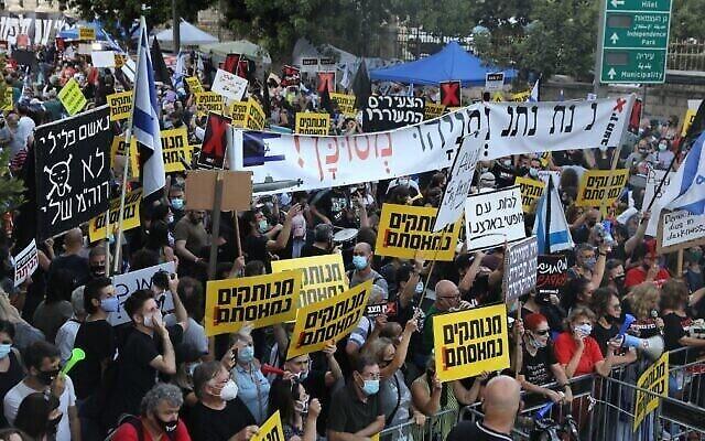 Les Israéliens protestent contre le Premier ministre Benjamin Netanyahu aux abords de sa résidence officielle à Jérusalem, le 14 juillet 2020 (Crédit : Menahem Kahana/AFP)