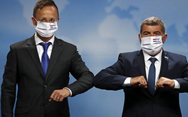 Le ministre hongrois des Affaires étrangères Péter Szijjártó (à gauche) et son homologue israélien Gabi Ashkenazi se saluent avec le coude lors de leur rencontre à Jérusalem, le 20 juillet 2020. (RONEN ZVULUN / POOL / AFP)