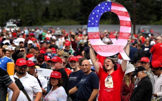 Un homme, David Reinert, brandit un grand panneau «Q» en attendant l'arrivée du président américain Donald Trump lors d'un rassemblement «Make America Great Again» au Mohegan Sun Arena de Casey Plaza, à Wilkes Barre, en Pennsylvanie, le 1er août 2018. (RICK LOOMIS / GETTY IMAGES AMÉRIQUE DU NORD / AFP)