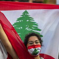 Une manifestante anti-gouvernement crie des slogans en portant un masque aux couleurs du drapeau libanais à Beyrouth, au Liban, le 2 juillet 2020. (Hassan Ammar / AP)