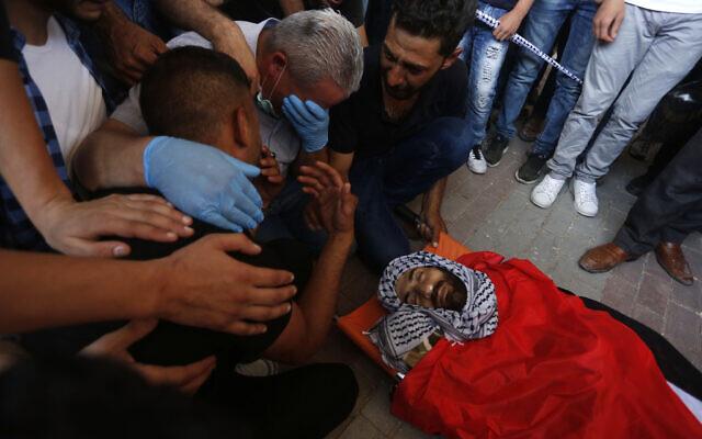Les proches pleurent autour de la dépouille d'Ibrahim Abu Yaqoub, 29 ans, tué dans des circonstances encore indéterminées en Cisjordanie, lors des funérailles de ce presque trentenaire, le 10 juillet 2020 (Crédit : WAFA)