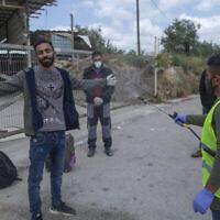 Un ambulancier du ministère de la Santé de l'Autorité palestinienne désinfecte des travailleurs palestiniens pour aider à contenir l'épidémie de coronavirus, alors qu'ils sortent d'un poste de contrôle après leur retour du travail en Israël, près du village cisjordanien de Nilin, à l'ouest de Ramallah, le 7 avril 2020. (Crédit : Nasser Nasser / AP)