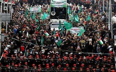 La police jordanienne en mission alors que les manifestants brandissent des drapeaux palestiniens et des Frères musulmans lors d'une manifestation contre la décision du président américain de reconnaître Jérusalem comme capitale d'Israël, dans la capitale jordanienne d'Amman, le 29 décembre 2017. (Khalil Mazraawi / AFP)
