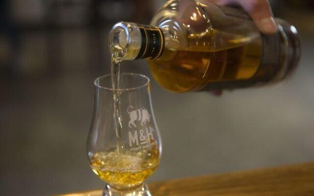 Sur cette photo du 10 août 2017, du whisky est versé à la distillerie de whisky Milk and Honey à Tel Aviv, Israël. (Autorisation : AP / Sebastian Scheiner)