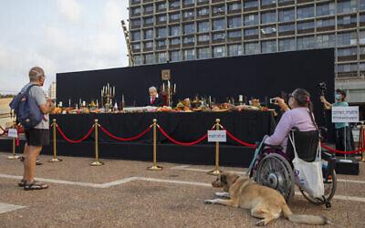 """Des passants prennent en photo l'installation de l'artiste israélien Itay Zalait se moquant du Premier ministre Benjamin Netanyahu en reprenant """"La Cène"""", sur la place Rabin à Tel Aviv, le 29 juillet 2020. (Crédit : Oded Balilty/AP)"""
