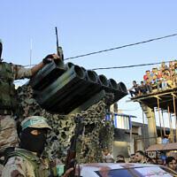 Photo d'illustration : Des membres du Hamas masqués à côté un lanceur de roquettes lors d'un rassemblement dans le camp de réfugiés de Rafah, dans la bande de Gaza, le 21 août 2016 (Crédit : AP Photo/Adel Hana)