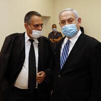 Le Premier ministre Benjamin Netanyahu, à droite, parle avec son avocat Micha Fettman, à gauche, dans la salle du tribunal lors de l'ouverture de son procès pour corruption à la cour de district de Jérusalem, le 24 mai 2020 (Crédit :  Ronen Zvulun/ Pool Photo via AP)