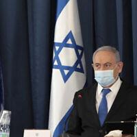 Le Premier ministre Benjamin Netanyahu porte un masque facial destiné à prévenir la propagation du coronavirus alors qu'il ouvre la réunion hebdomadaire de son cabinet, au ministère des Affaires étrangères, à Jérusalem, le 5 juillet 2020. (Gali Tibbon/AP)