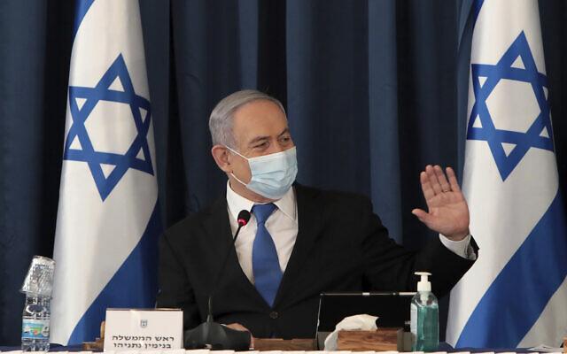 Le Premier ministre Benjamin Netanyahu porte un masque facial pour contribuer à prévenir la propagation du coronavirus alors qu'il préside la réunion hebdomadaire du cabinet, au ministère des Affaires étrangères, à Jérusalem, le 5 juillet 2020. (Gali Tibbon/Pool via AP)
