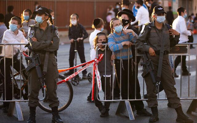 Des agents de la police des frontières à un barrage routier alors que des Juifs ultra-orthodoxes se rassemblent pour protester contre le bouclage de leur quartier en raison d'une épidémie de coronavirus, à Jérusalem, le 13 juillet 2020. (AP Photo/Oded Balilty)