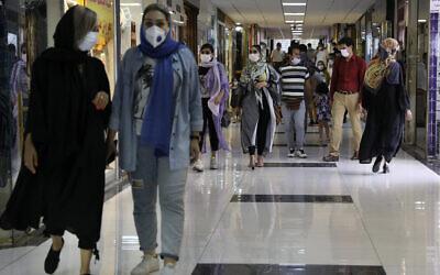 Des personnes portant des masques de protection pour lutter contre la propagation du coronavirus traversent le centre commercial Nasr à Téhéran, en Iran, le 15 juillet 2020. (AP Photo/Vahid Salemi)
