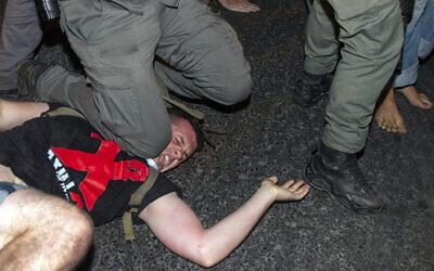 Un officier de police israélien met son genou sur le coup d'un manifestant pour procéder à son arrestation lors d'une manifestation contre le Premier ministre Benjamin Netanyahu, devant sa résidence à Jérusalem, le 22 juillet 2020. (AP Photo/Ariel Schalit)