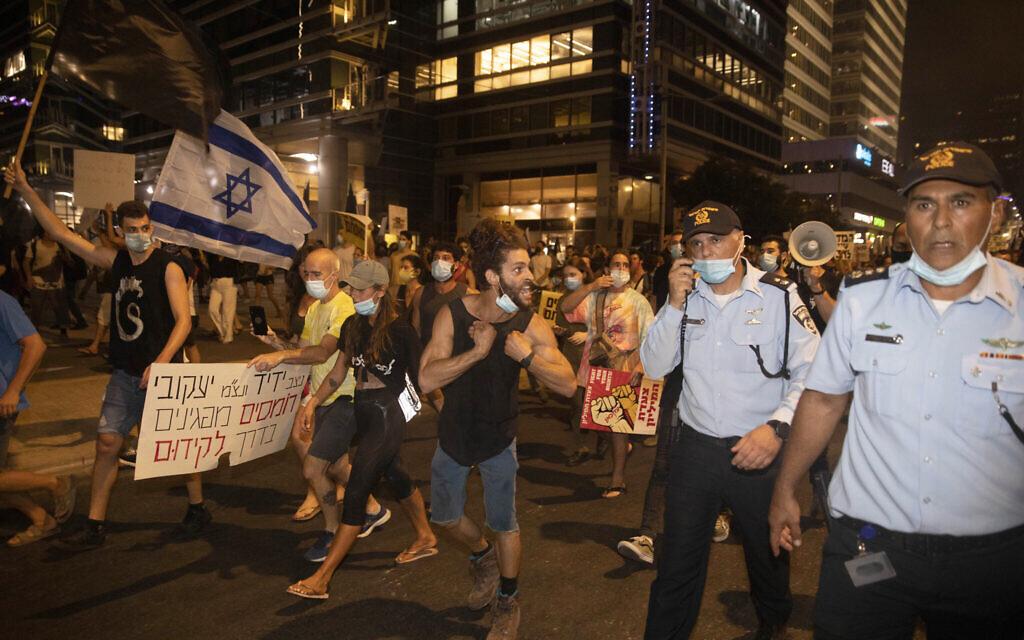 Un manifestant israélien se dispute avec des officiers de police lors d'une manifestation contre la corruption près de la maison du ministre israélien de la Sécurité publique à Tel Aviv, mardi 28 juillet 2020. (AP Photo/Sebastian Scheiner)