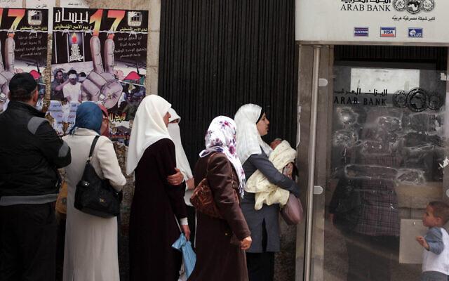Des Palestiniens reçoivent leurs salaires dans une banque de Ramallah, en Cisjordanie, le 17 mai 2011 (Crédit : Issam Rimawi/FLASH90)