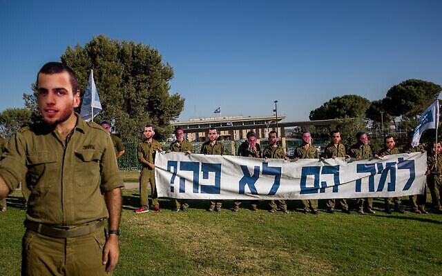 Des amis des soldats Oron Shaul et Hadar Goldin portent des masques à leur effigie pour réclamer le retour de leurs dépouilles, devant la Knesset le 1er juillet 2020. (Crédit : Yonatan Sindel/Flash90)