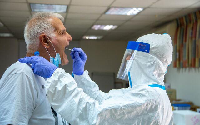 Des personnels soignants recueillent des échantillons pour effectuer des tests de dépistage au coronavirus dans un centre de santé Clalilt,à Lod, le 25 juillet 2020 (Crédit : Yossi Aloni/FLASH90)