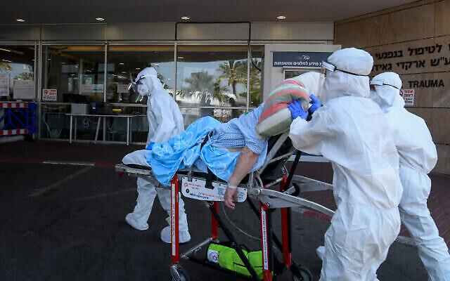 Des employés du Magen David Adom portant des vêtements de protection transfèrent un patient à l'unité de lutte contre le coronavirus au centre médical Sheba à Ramat Gan, le 8 juillet 2020. (Flash90)