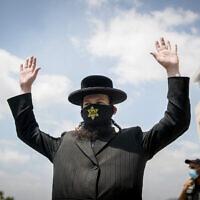 Un Juif ultra-orthodoxe arbore un masque avec une étoile jaune et lève les mains à un barrage routier du quartier   Hephzibah à Beit Shemesh actuellement placé sous confinement pour prévenir la propagation du coronavirus, le 10 juillet 2020 (Crédit :  Yonatan Sindel/Flash90)