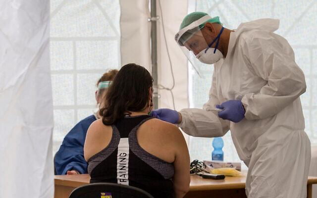 Des personnels soignants effectuent des tests sur des résidents sur un site temporaire pour collecter des échantillons du coronavirus, dans le sud de Tel Aviv, le 16 juillet 2020 (Crédit : Flash90)