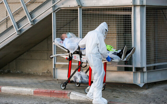 Un salarié du Magen David Adom portant des vêtements de protection évacue un patient atteint du coronavirus à l'extérieur de l'unité coronavirus du centre médical Ziv dans la ville de Tzfat, dans le nord d'Israël, le 19 juillet 2020. (David Cohen / Flash90)