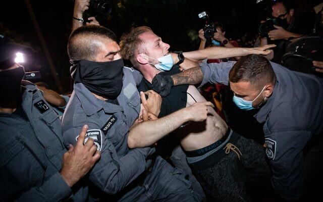 La police fait partir des manifestants pendant un rassemblement contre le Premier ministre Benjamin Netanyahu aux abords de sa résidence officielle de Jérusalem, le 25 juillet 2020 (Crédit:  Yonatan Sindel/Flash90)