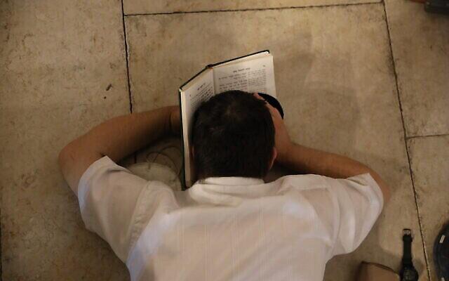 Un homme juif prie au mur Occidental la nuit de Tisha BeAv dans la Vieille Ville de Jérusalem, le 29 juillet 2020. (Olivier Fitoussi/Flash90)