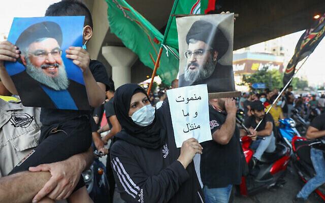 Des partisans du Hezbollah brandissent des photos de son chef terroriste Hassan Nasrallah et des pancartes anti-américaines alors qu'ils protestent contre une déclaration de l'ambassadrice américaine critiquant le groupe lors d'un rassemblement dans la banlieue sud de la capitale Beyrouth, le 28 juin 2020. (Anwar Amro/AFP)