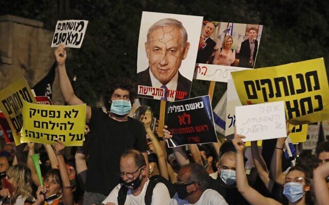 Des manifestants israéliens tiennent des pancartes lors d'une manifestation contre le Premier ministre Benjamin Netanyahu à Jérusalem, le 23 juillet 2020. (Photo par Ahmad GHARABLI / AFP)