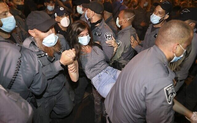 Une femme est arrêtée lors d'une manifestation contre le Premier ministre israélien à Jérusalem, le 23 juillet 2020. (Photo par MENAHEM KAHANA / AFP)