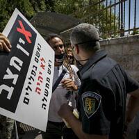 Un inspecteur de la municipalité de Jérusalem parle à manifestant à proximité de la résidence officielle du Premier ministre Benjamin Netanyahu  à Jérusalem le 13 juillet 2020. (Olivier Fitoussi/Flash90)