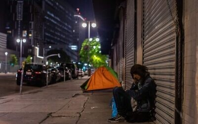 On peut voir une femme sans domicile fixe dormir dans la rue Skid Row pendant le COVID-19, l'épidémie de coronavirus à Los Angeles, en Californie le 16 mai 2020. (Apu Gomes/AFP via Getty Images)