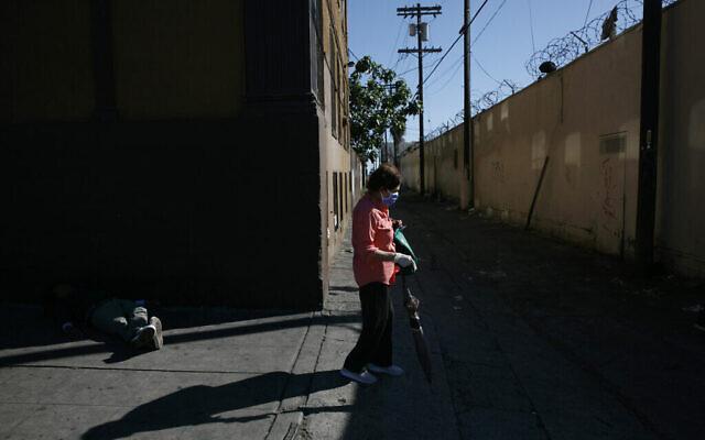 Une femme avec un masque et des gants de protection passe à côté d'un sans-abri endormi dans une rue en pleine épidémie de coronavirus dans le quartier de Westlake de Los Angeles, le jeudi 21 mai 2020. (AP Photo/Jae C. Hong)