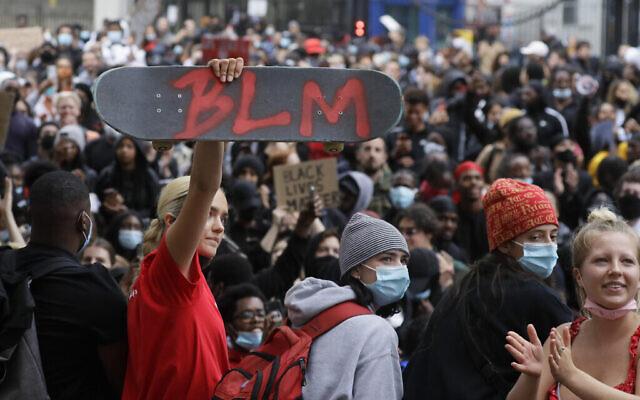 Un manifestant tient une planche de skateboard avec les initiales de Black Lives Matter à Londres, le mercredi 3 juin 2020 lors d'une manifestation après la mort de George Floyd, un homme noir qui es mort après avoir été maîtrisé par des officiers de police à Minneapolis le 25 mai. (AP Photo/Kirsty Wigglesworth)