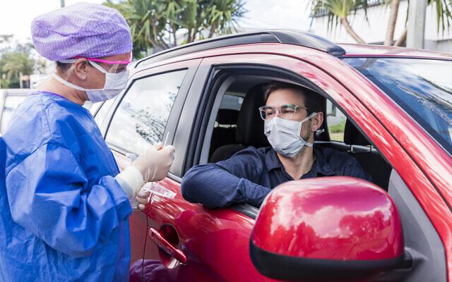 Une médecin vêtue d'une combinaison de protection effectue un test au coronavirus. (iStock)