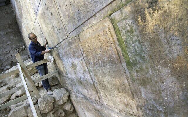 L'archéologue Joe Uziel nettoie les parties du mur Occidental récemment mises à jour, situées sous l'Arche de Wilson dans la Vieille Ville de Jérusalem, octobre 2017. (Yaniv Berman/Autorité israélienne des Antiquités)