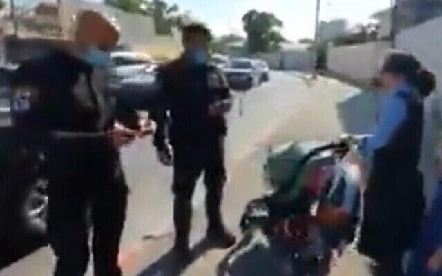 La police arrête une jeune fille ultra-orthodoxe à Jérusalem pour défaut du port correct du masque, le 6 juillet 2020 (Capture écran/Twitter)