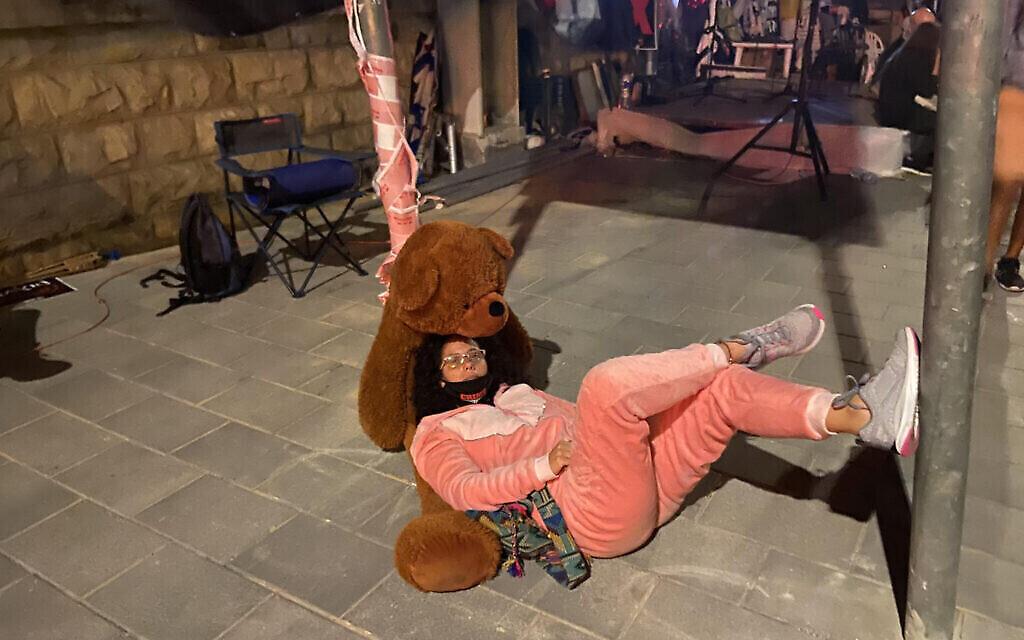 Mirav Ben-Uziel, en pyjama rose et avec son ours en peluche, devant la résidence du Premier ministre à Jérusalem, le 16 juillet 2020. (Anat Peled)