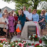 Une famille polonaise devant un mémorial honorant ses proches qui ont tenté de sauver des Juifs pendant la Seconde Guerre mondiale. (Avec l'aimable autorisation de l'Institut Pilecki)