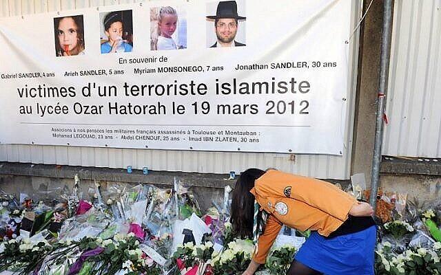 """Un éclaireur israélite français place des fleurs sous une bannière rendant hommage aux victimes de l'attentat contre l'école juive """"Ozar Hatorah"""", à Toulouse, le 25 mars 2012. (AFP / ERIC CABANIS)"""