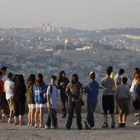 Un groupe touristique écoute un guide sur la promenade  Armon Hanatziv de Jérusalem avec la Vieille Ville en arrière-plan, en 2018 (Crédit : Miriam Alster/Flash90)