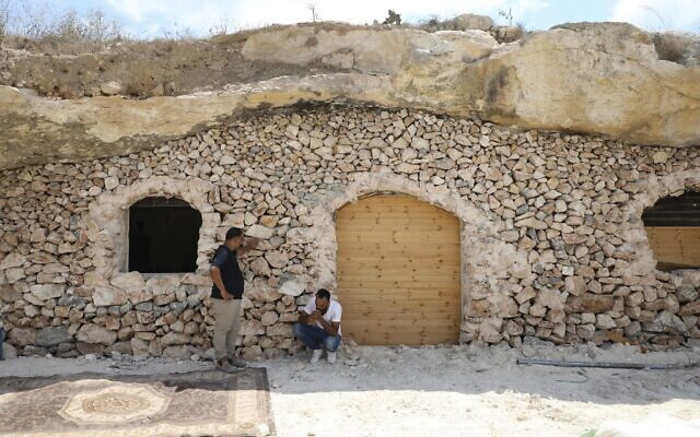 Ahmed Amarneh et un voisin discutent devant sa maison, construite dans une grotte du village de Farasin, à l'ouest de Jénine, dans le nord de la Cisjordanie, le 4 août 2020. (Photo de JAAFAR ASHTIYEH / AFP)